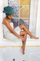 woman sitting on the windowsill and shaves his legs