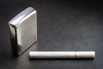 Lighter and one cigarette on dark background. Selective focus.