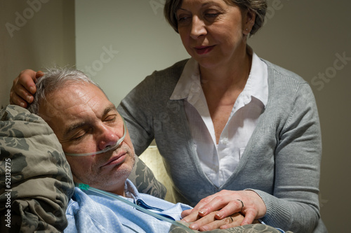 Caring nurse with sleeping senior male patient