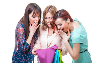 Surprised girl friends looking into shopping bag