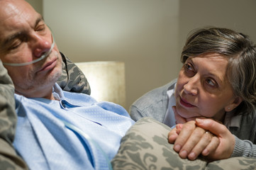 Anxious old woman taking care of husband