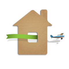 House cut out of cardboard with airplane