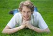 Student liegt auf der Wiese und strahlt