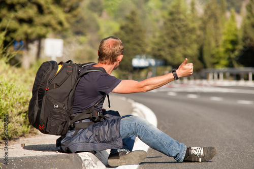 Hitchhiker man traveler sitting on the roadside