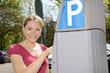 Junge Frau bedient Parkscheinautomaten