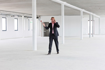 Business man in crisis walking and calling in empty office.