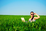 happy girl in a green field with a laptop. summer