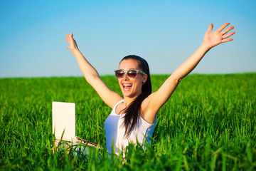 happy freelancer girl in a green field with outstretched arms