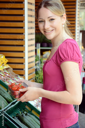 Junge Frau kauft Erdbeeren