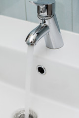 Tap with flowing water over the sink