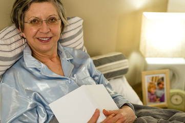 Old woman in pajamas lying in bed