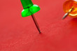 Colorful pushpins on a red surface