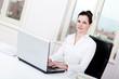 Junge Brünette Business Frau mit einem Laptop an einem Schreibt