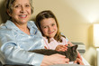 Cheerful senior woman with granddaughter and cat