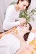 Junge brunette Frau bei einer pflegenden Gesichtsmaske mit Kosme