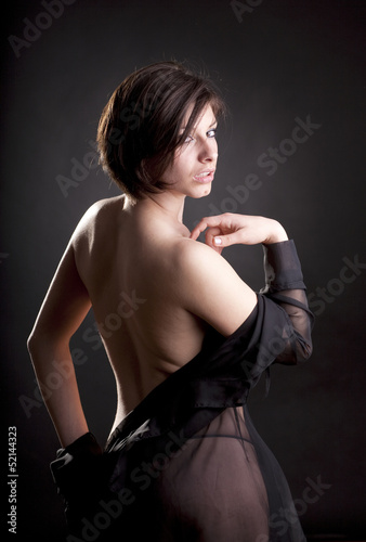 Portrait of sexy brunette nude woman wrapped with black tulle
