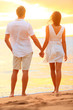 Young couple holding hands at beach sunset