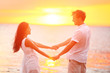 Romantic couple lovers holding hands, beach sunset