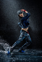 Wet dancing woman. Under waterdrops. Studio photo