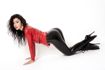 Sexy flexible brunette woman in black and red latex and boots
