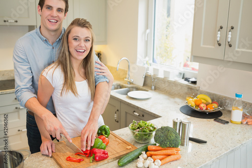 Couple smiling and working in the kitchen