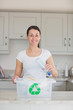 Smiling woman throwing bottle into recycling bin