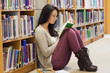Student leaning against a shelf in a library