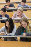 Students learning in a lecture hall with one girl using tablet