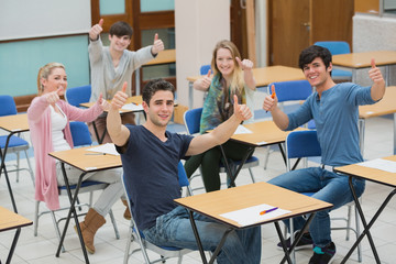 Students in classroom giving thumbs up