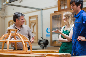 Students and teacher talking and laughing in woodwork class