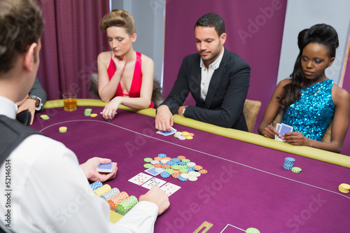 Man and two women playing poker