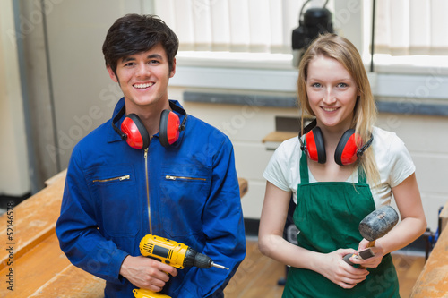 Two students holding a driller and a hammer