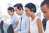 Smiling call center employees sitting in line