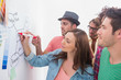 Creative team watching colleague add to flowchart