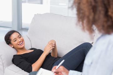 Woman lying on therapists couch looking happy