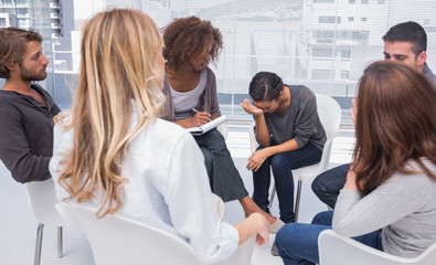 Group therapy session with one woman crying