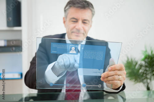 Businessman using futuristic touchscreen to view social media pr