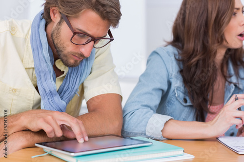 Editor using tablet at meeting as colleague is talking