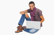 Happy man sitting on floor using laptop looking at camera