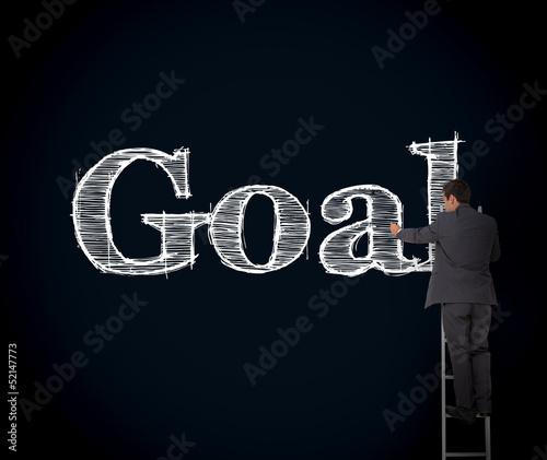 Businessman writing goal on a giant blackboard