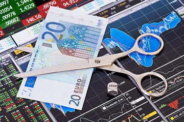 Scissors cutting  euro  banknote, dices cube with the word STOP.