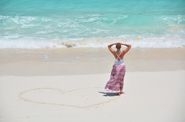 Girl drawing a heart on the sandy beach