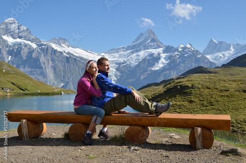 Travelers on a bench enjoying Alpine panorama. Jungfrau region,