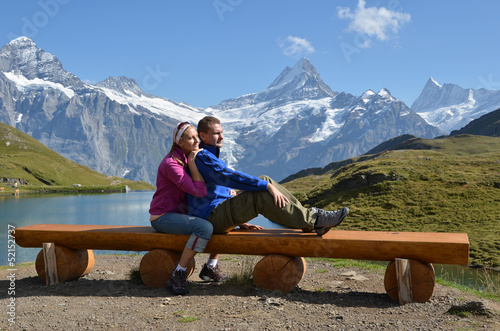 Travelers on a bench enjoying Alpine panorama. Jungfrau region,