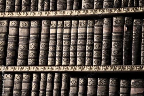 Old books in a library - sepia image