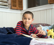 Young Boy Reading in Bed with Workbook