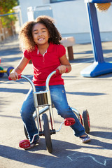 Child Riding Tricycle In Playground