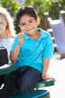 Elementary Pupil Sitting At Table Eating Lunch