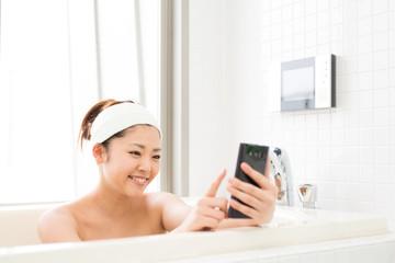 風呂でスマホを見る女性