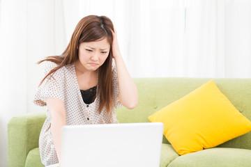 部屋でパソコンを使う女性 トラブル
